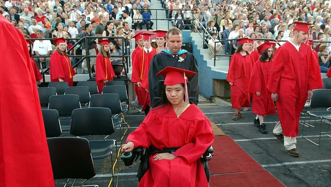 Ty Becker, in the black gown, escorted student Insai Thao at the 2002 Wausau East High School graduation ceremony.