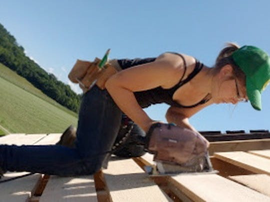 Cari Stebbins nails boards high atop the barn roof.