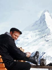 In this undated photo provided by the Warren Miller Co., Warren Miller is shown lacing up his boots in view of the Matterhorn.