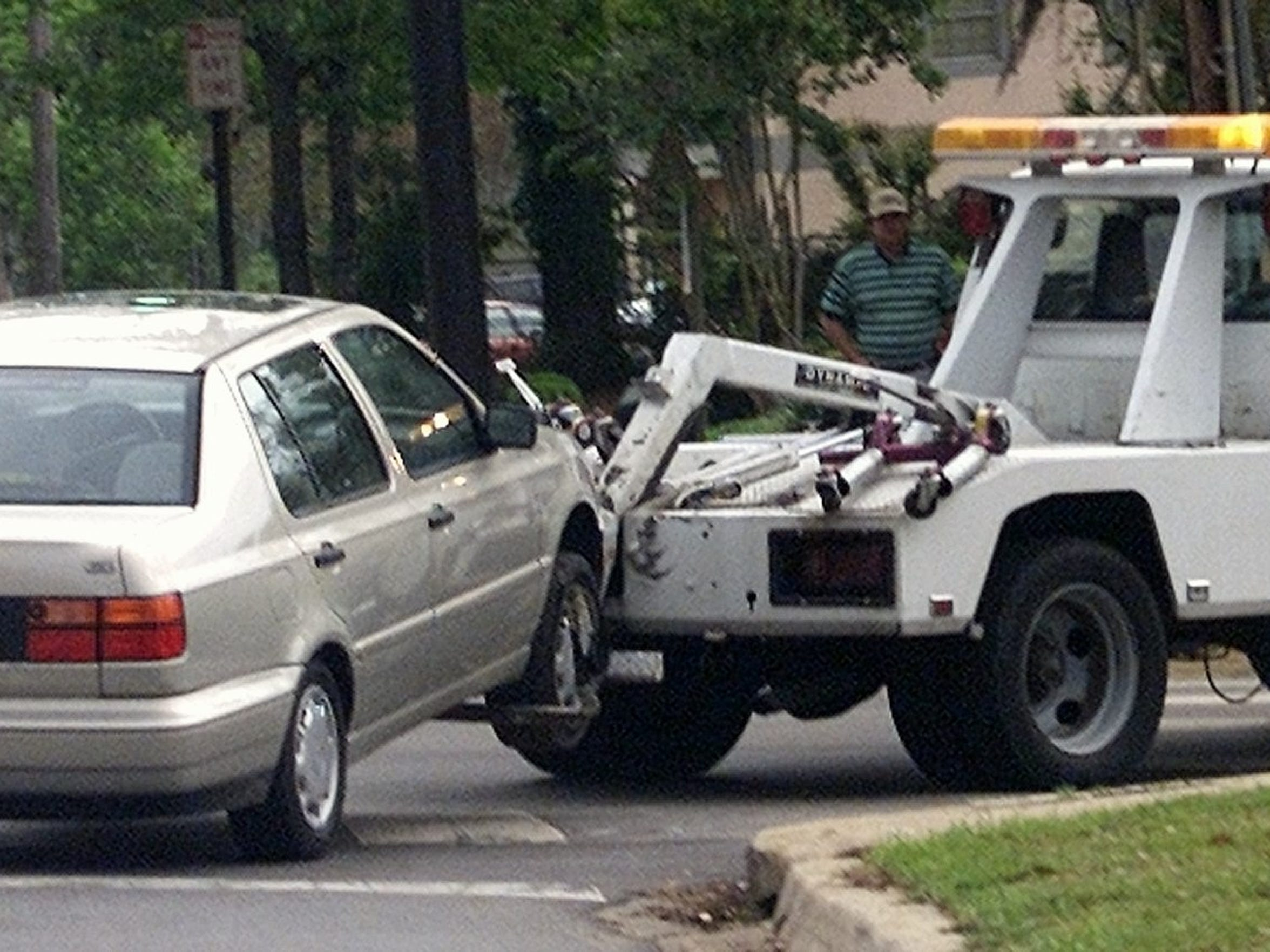 A car is towed away from an FSU parking lot by a DeLoach truck.