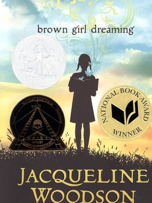 An edition of the cover of Brown Girl Dreaming with three medals on it.