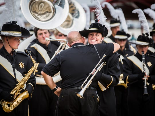 Band director Douglas Fletcher hugs Winchester band members before preliminaries at the Indiana State Fair Saturday.  Fletcher retired as band director following the Band Day competition.