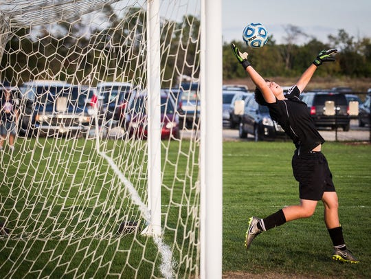 Central's Riley Stafford stops a kick from Delta during