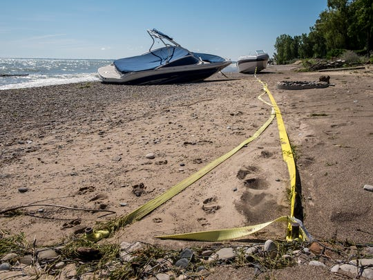 Tow straps are used to secure damaged boats on a beach on Lake Huron in Burtchville Township. The boats were pulled onto the beach when a north wind blew in Monday.