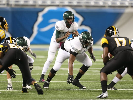 Cass Tech's Rodney Hall takes a snap during first quarter action against Detroit Martin Luther King on Friday, October 24, 2014 at Ford Field in Detroit.