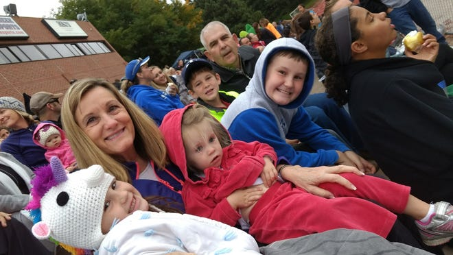 Sophia, Scarlet, Isaac and Stratton Anderson snuggle up with their grandparents, Cindy and Scott Hadley, as they wait for a sibling's event. The Andersons participate in activities and root for each other.