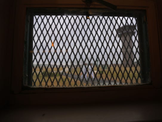 Inmates walk past a security tower seen through a window of the Chapel at James T. Vaughn Correctional Center. Feb. 1 will mark the one-year anniversary of the deadly siege that killed correctional officer Lt. Steven Floyd.