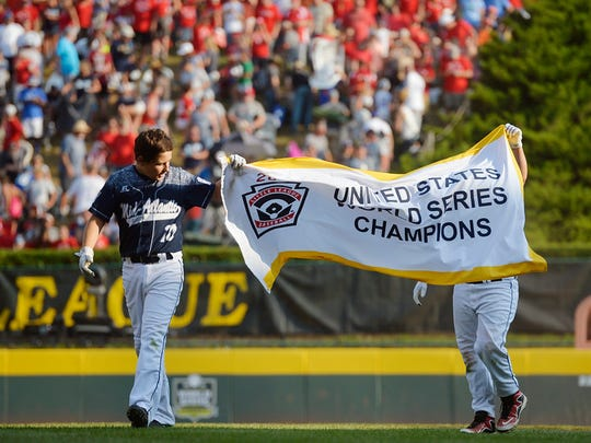 """Red Land's Adam Cramer and Ethan Phillips carry the U.S. champion flag Saturday, Aug. 29, 2015, after winning the Little League World Series U.S. championship game featuring Red Land Little League of Pennsylvania and Pearland West Little League of Texas, in South Williamsport. Red Land defeated Pearland 3-2 in a walk-off victory to move on to the world championship game against Tokyo Kitasuna of Japan."