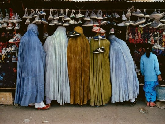Women shop for shoes in this work by Steve McCurry. 'Women at Shoe Store, Kabul, Afghanistan,' is a 1992 archival pigment print, part of the Michener show.