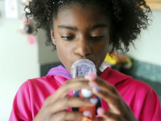 Coryne Davis, 12, uses an inhaler to help with her asthma before eating breakfast in her North Codorus Township home. Coryne and her sister Cameron, 9, who also suffers from asthma, have attended Camp Green Zone, which helps teach kids how to care for their symptoms. (Jason Plotkin -- Daily Record/Sunday News)