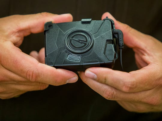 New Castle County police officer Tom Jackson shows the storage unit for a shoulder-mounted body camera the department tested on Friday afternoon.