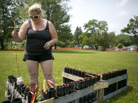 Amy Spader of Oshkosh loads shells into plastic tubes Sunday at Mead Park as she helps set up for the fireworks display for Riverfront Rendezvous in Stevens Point.