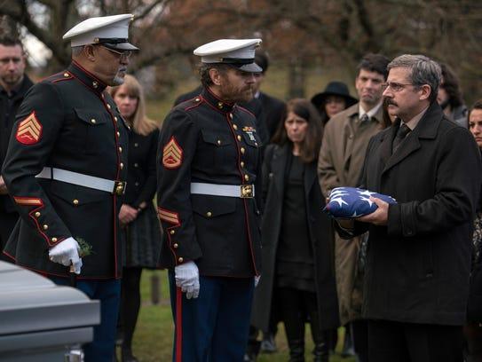 Mueller (Laurence Fishburne, left) and Sal (Bryan Cranston) help Larry (Steve Carell) bury his son in 'Last Flag Flying.'