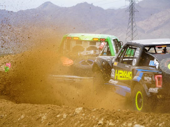 Racers throw dirt as they jockey for position in a