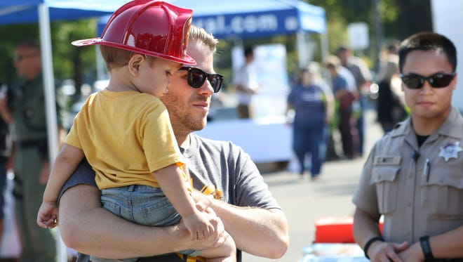 Travis Gray of Albany and his 2-year-old son, Cohen, learn about how to prepare for natural disasters during Get Ready Salem on Saturday, Sept. 12, 2015, at the Oregon State Capitol. September is National Preparedness Month. The free event provided lunch and safety demonstrations by local law enforcement and emergency groups, among other activities.