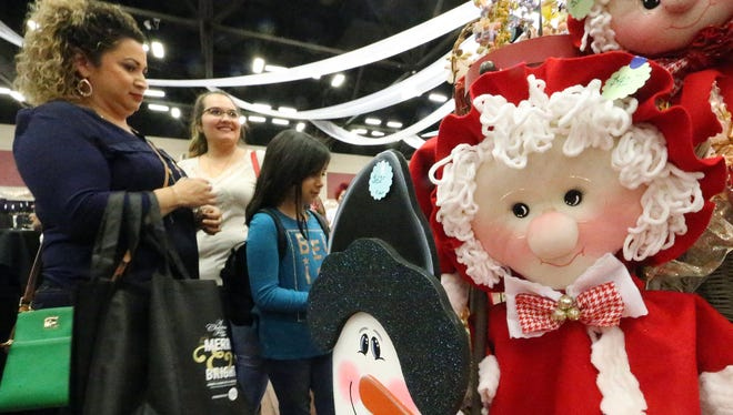 Marie Terrazas, left, looks at Christmas-themed items for sale with daughter Zoey Terrazas, 8, Friday at the Junior League of El Paso's A Christmas Fair.