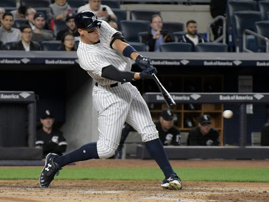 In this Monday, April 17, 2017, photo, New York Yankees right fielder Aaron Judge hits a two-run home run during the fifth inning of a baseball game against the Chicago White Sox at Yankee Stadium in New York. Judge has transformed batting practice in the Bronx, where the Yankees are raising the top of their batting cage to accommodate the 6-foot-7 slugger. (AP Photo/Bill Kostroun)