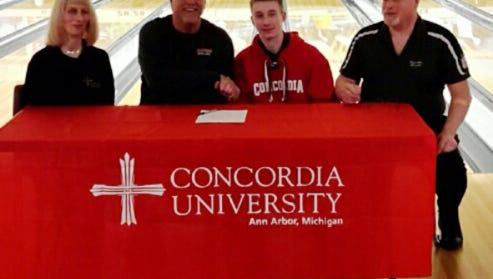Nick Bell is congratulated by Concordia University head coach Doug Spicer as his parents, Cathy and George look on.