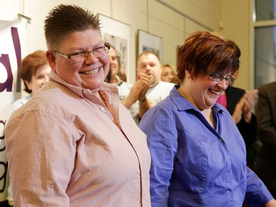 Jayne Rowse, left, and her partner April DeBoer smile as a crowd applauds them.