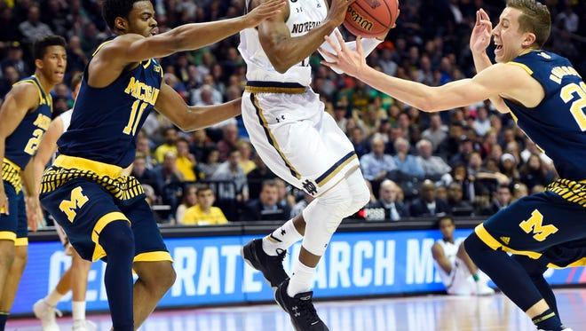 Notre Dame guard Demetrius Jackson (11) tries to get past Michigan guard Derrick Walton Jr. (10) and guard Duncan Robinson (22) in the first half Friday in Brooklyn, N.Y.