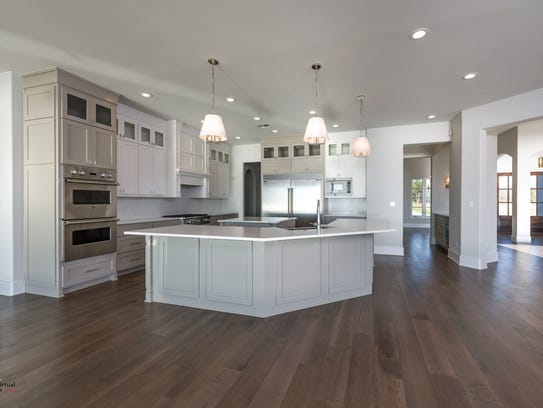 The kitchen features double ovens, a six-burner gas