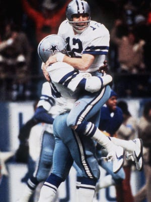 Roger Staubach (12) celebrating after throwing a touchdown pass in a 1975 game, threw his famed Hail Mary pass in the playoffs that season to lift the Cowboys over the Vikings.