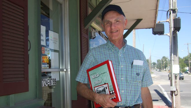 """Local author and radio broadcaster Wayne Glenn posed for a portrait in front of a Nixa business in Sept. 2012 with a book he published that year, """"Nixa as Mayberry."""" Glenn celebrates his 2,000th consecutive Saturday-morning radio show as """"The Old Record Collector"""" on Dec. 10, 2016."""