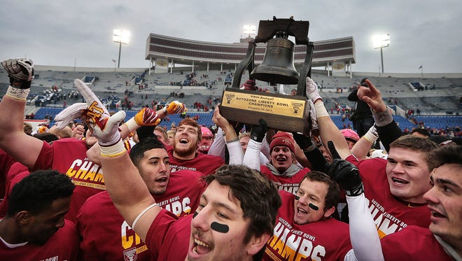 Iowa State players celebrate with the trophy after beating the University of Memphis 21-20 to win the 59th annual Liberty Bowl in Memphis Saturday.