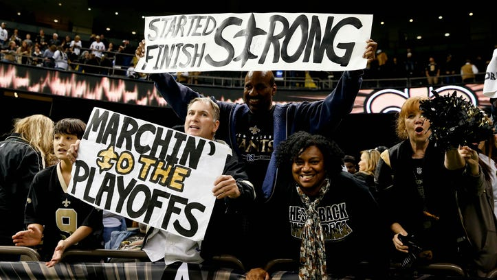 Dec 29, 2013; New Orleans, LA, USA; New Orleans Saints fans Larry Rolling (bottom) holds up a sign following a win over the Tampa Bay Buccaneers in a game at the Mercedes-Benz Superdome.The Saints defeated the Buccaneers 42-17.
