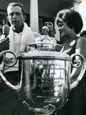 Standing behind the Wanamaker trophy that goes to the PGA Championship winner, Bobby Nichols is interviewed following his 1964 victory. At right is his wife Nancy.