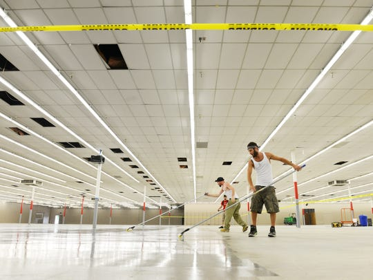 Todd Vella, right, Joshawa Carpenter and Trenton Carpenter of Ashley Construction seal the floor of the under-construction Rural King in South Zanesville. The store is expected to open in August.