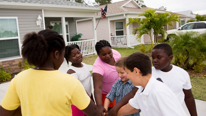 Neighborhood children, from left, Fabiana Jean-Baptiste, 9, Leoneyika Cetlute, 10, Fedena Brutus, 11, Sevrin Evans, 8, his brother Mikael, 12, and Felix Brutus, 9, all of whom live in the Legacy Lakes community, play outside on April 11, 2017, in Naples. The community of 55 homes, built by Habitat for Humanity of Collier County, allows families to afford a new home after a rigorous application process in a safe neighborhood.