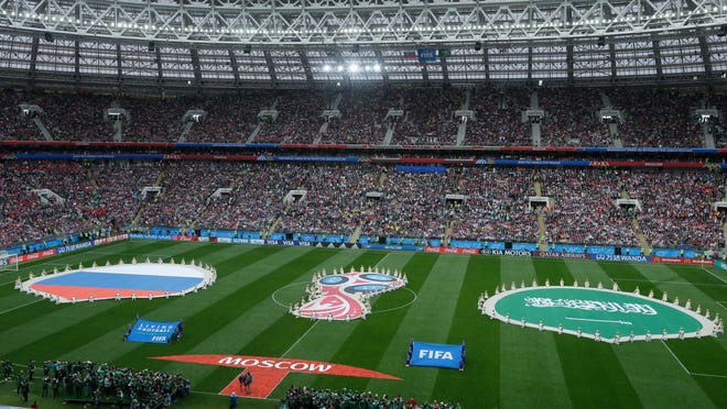 Performers display the 2018 World Cup logo and the colors of Russia and Saudi Arabia prior to their group A match Thursday.