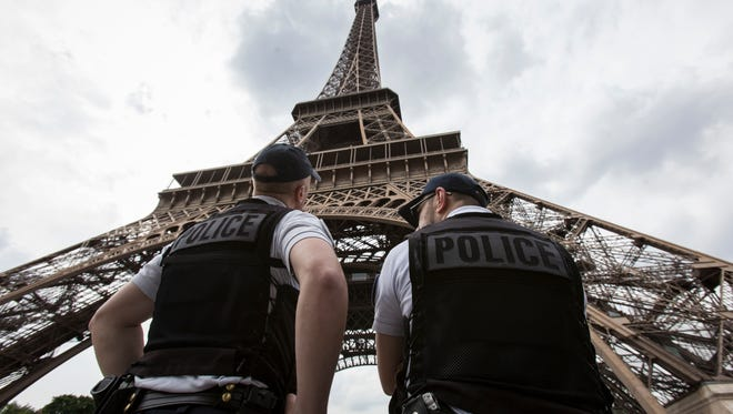 FILE- In this Friday, June 10, 2016 file photo, French riot police officers patrol under the Eiffel Tower, near the entrance of the soccer fan zone, prior to the Euro 2016 Group A soccer match between France and Romania, in Paris. Paris authorities say Thursday, Feb. 9, 2017, they are proposing to replace the metal security fencing around the Eiffel Tower with a more aesthetic glass wall.