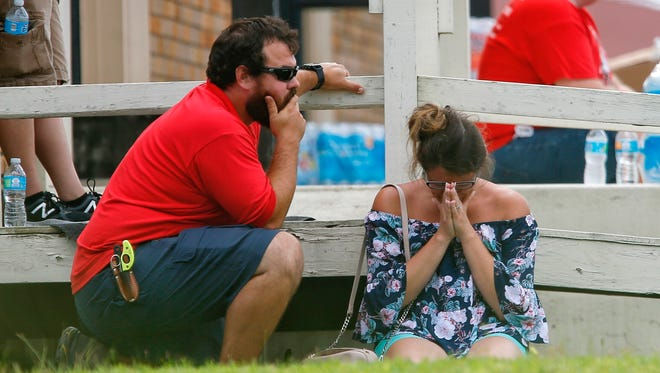 A woman prays in the grass outside the Alamo Gym where parents wait to reunite with their kids following a shooting at Santa Fe High School in Santa Fe, Texas, May 18, 2018.
