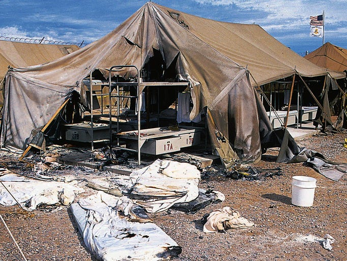 Oct. 1994: Charred mattresses are spread out in front