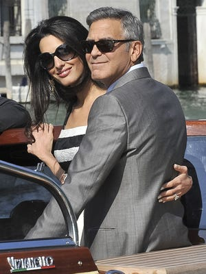 George Clooney and his fiancée, Amal Alamuddin, arrive in Venice, Italy, on Friday. Celebrities including Cindy Crawford and Matt Damon also traveled to Venice Friday for the weekend wedding.