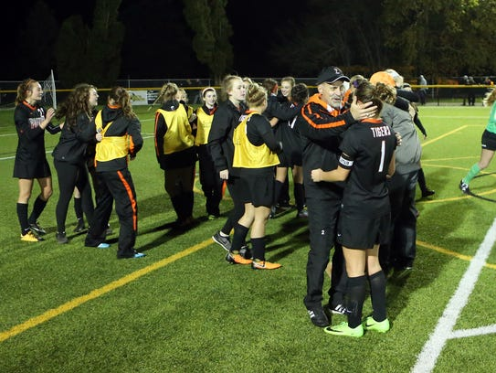 Loveland Head Coach Todd Kelly has a big hug for striker