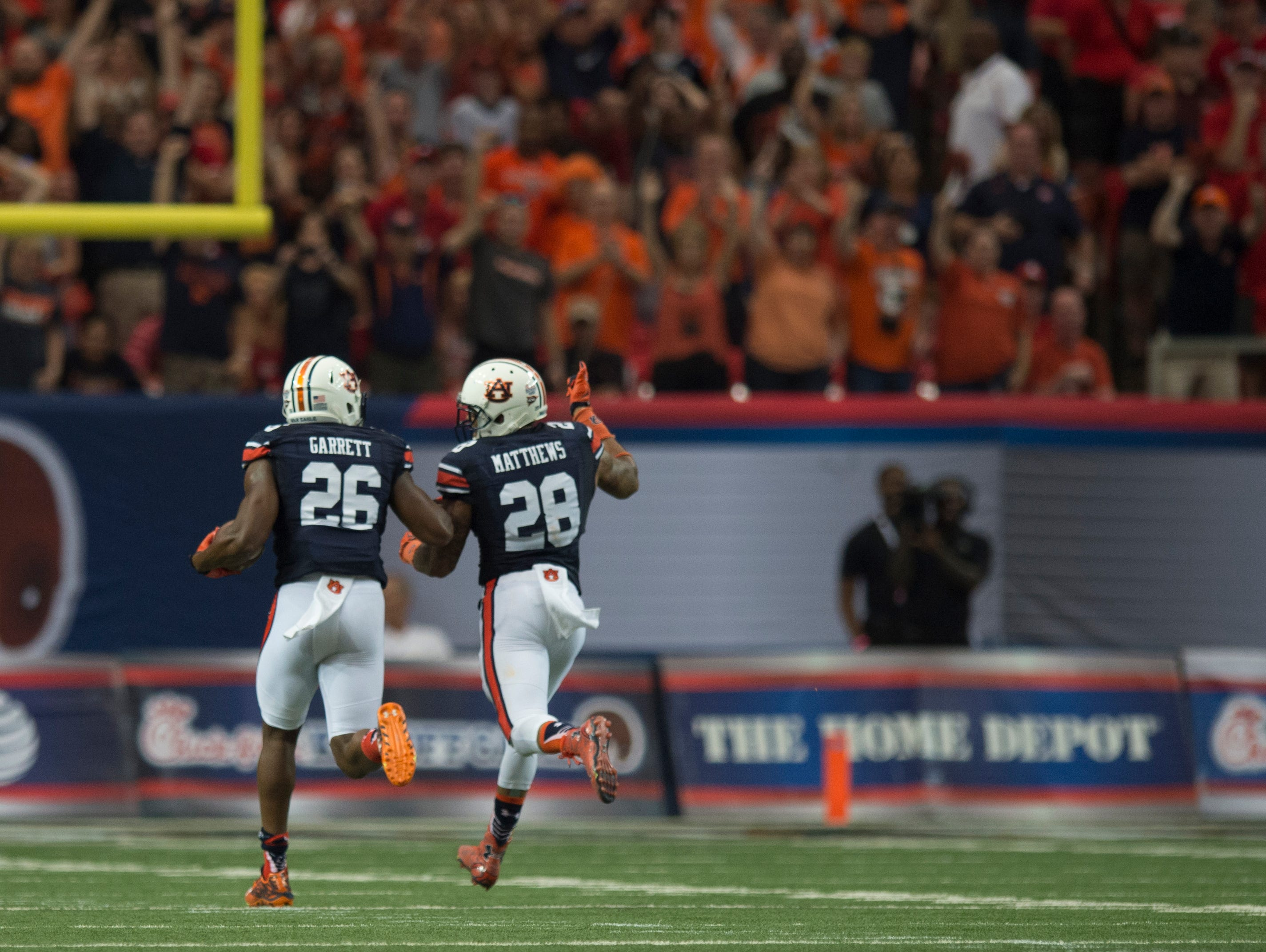 Auburn linebacker Justin Garrett (26) picks up a fumble and returns it for a touchdown during the NCAA football game between Auburn and Louisville on Saturday, Sept. 5, 2015, in at the Georgia Dome in Atlanta, Ga.