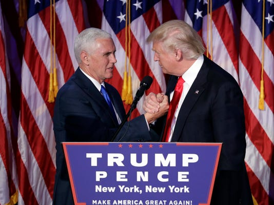 President-elect Donald Trump shakes hands with Vice President-elect Mike Pence as he gives his acceptance speech during his election night rally, Wednesday, Nov. 9, 2016, in New York. (AP Photo/John Locher)
