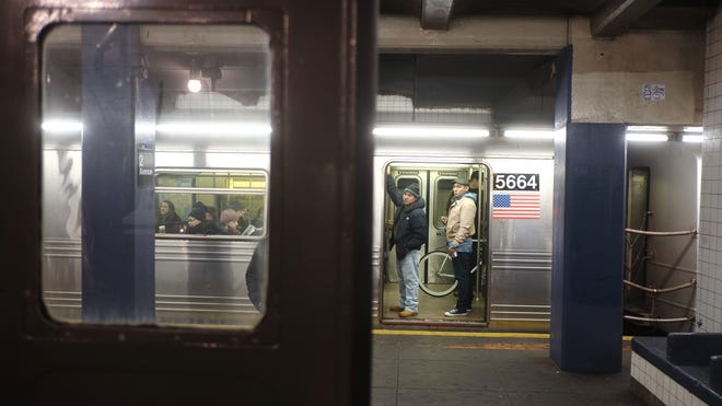 """People look over at the Metropolitan Transit Authority """"Nostalgia"""" vintage subway train from a F train on the opposite track in New York City."""