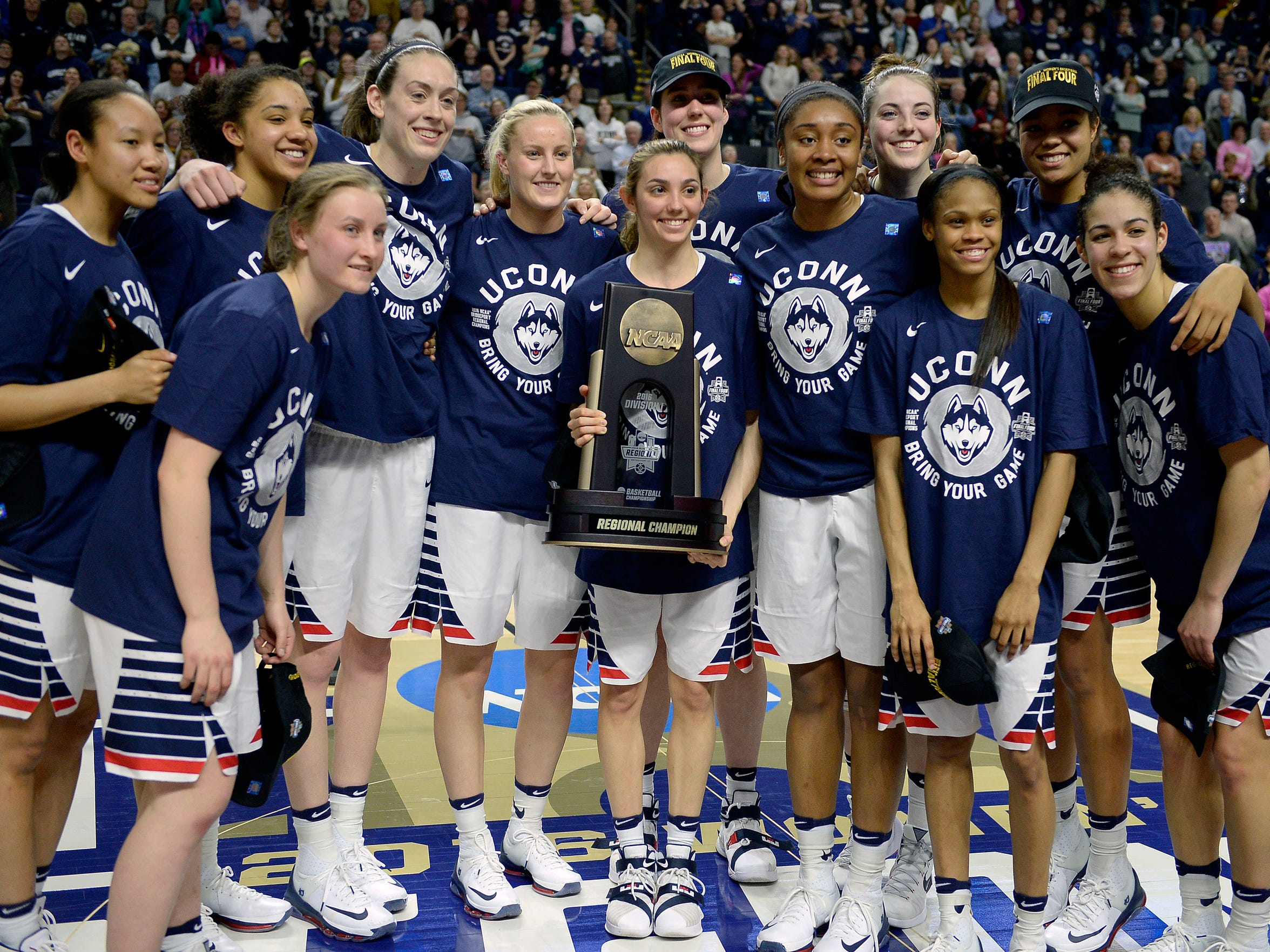 Connecticut''s Briana Pulido holds the trophy as the team poses after winning 86-65 over Texas in a college basketball game in the regional final of the women's NCAA Tournament, Monday, March 28, 2016, in Bridgeport, Conn.