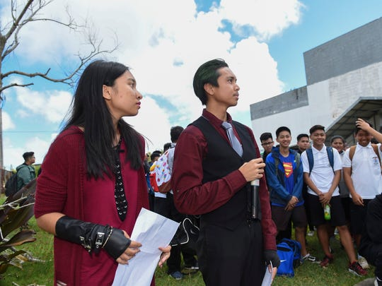 Protest organizers and Simon Sanchez High School students Nestor Casin, 17, and Hacie San Jose, 16, look to their fellow student protestors at their school campus in Yigo on Oct. 30, 2017. Casin and Hacie, along with hundreds of other Sanchez students, gathered by the school statue to protest for urgency in the rebuilding of their dilapidated school.