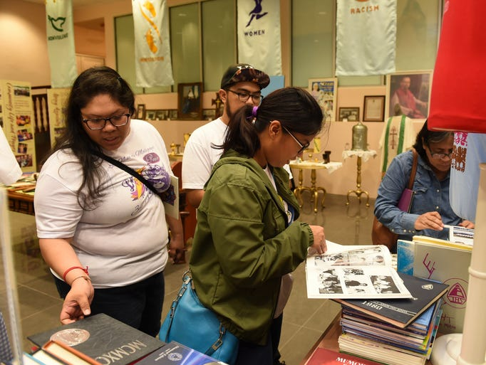 Museum patrons examine old yearbooks in the Sisters