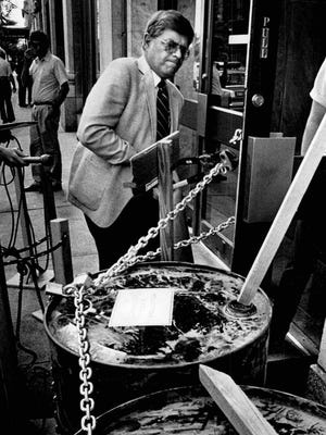 Bob Stein, security officer for RG&E, snips chains binding barrels of supposedly contaminated water to the front door of East Ave. headquarters in 1985.