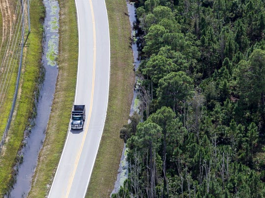 A dump truck drives along rural Corkscrew Road in Lee