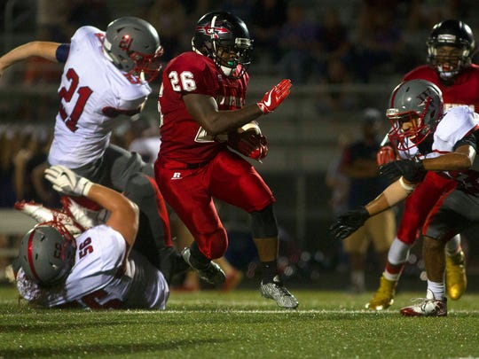 Liberty's Cavaugio Butler (26) carries the ball while trying to avoid the tackle by West Oak's Ryan Butts (21) on Friday, September 22, 2017 at Liberty High in Liberty.