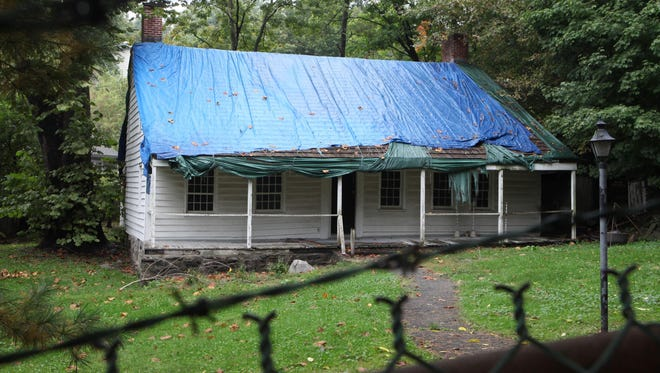 The Miller House in North White Plains sits under a tarp and behind locked gates in this October 2012 file photo.