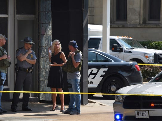 Officials consult near the crime scene at the Huntington