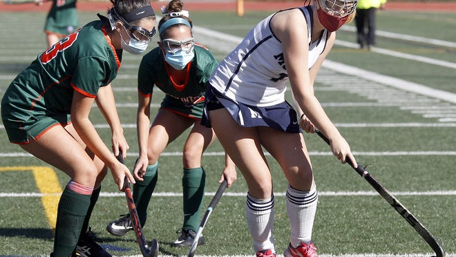 Medway's Sophie Donovan (right) shields the ball against Hopkinton's Sophie Driscoll (left) and Sarah Doyle during Sunday's field hockey game at Medway High.